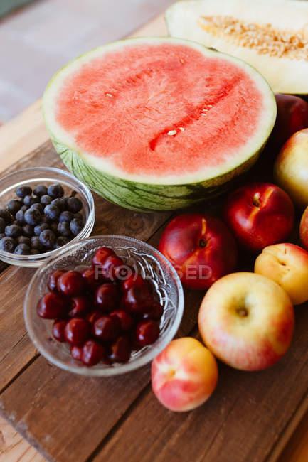 Deliciosas frutas e bagas de verão na mesa de madeira rústica — Fotografia de Stock