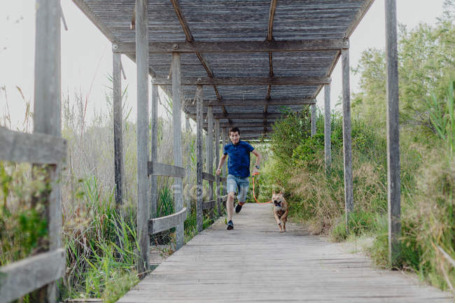 Happy mid adult man running with dog along countryside — Stock Photo