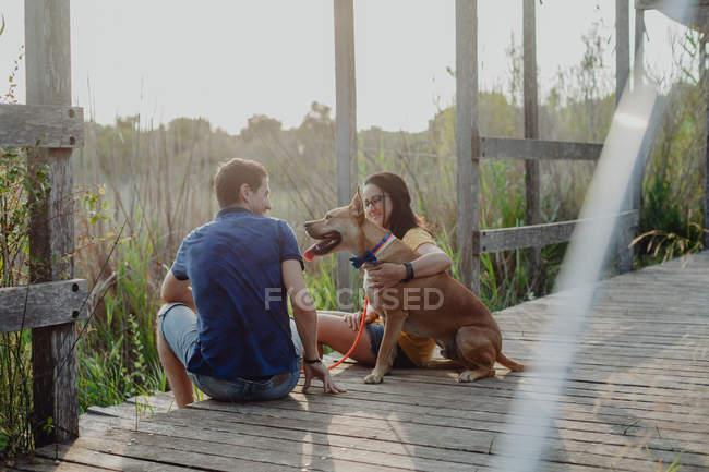 Casal alegre relaxante com cão no campo — Fotografia de Stock