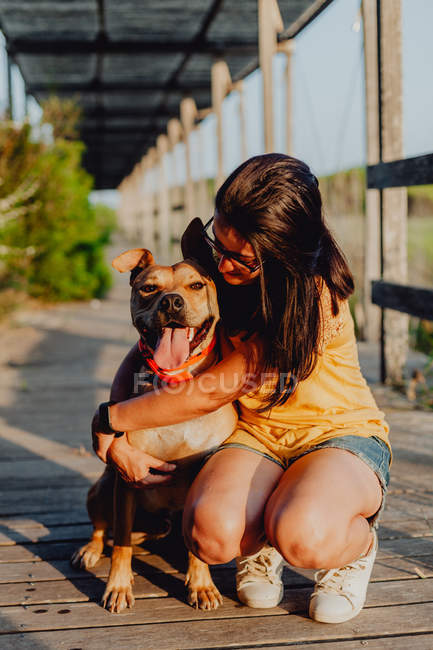 Cheerful casual young woman in sunglasses embracing playful brown dog on leash — Stock Photo