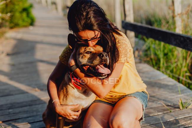 Felice giovane donna che abbraccia allegro cane in campagna — Foto stock