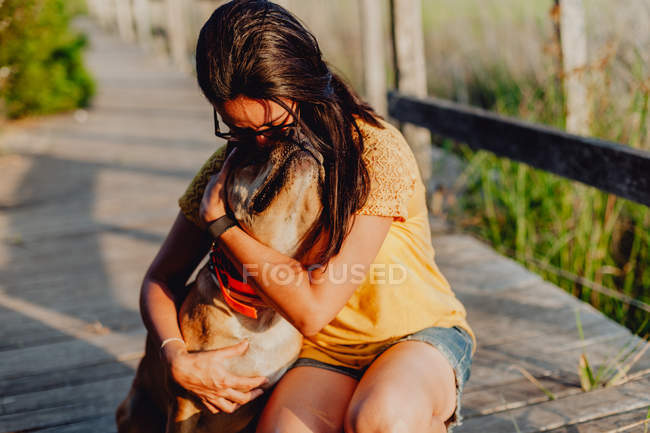 Happy woman embracing dog at countryside wooden terrace — Stock Photo