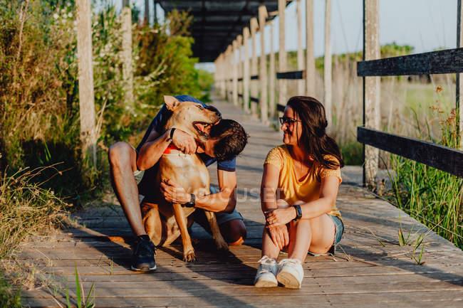 Coppia felice divertirsi con il cane sulla terrazza in legno campagna — Foto stock