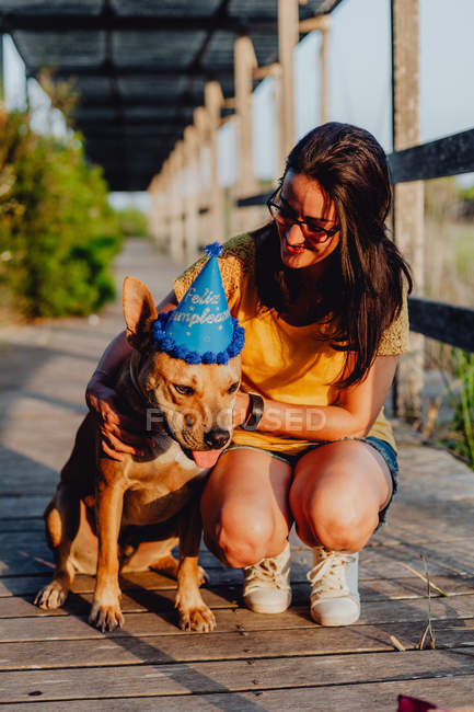 Casual young woman resting next to brown dog with party hat — Stock Photo