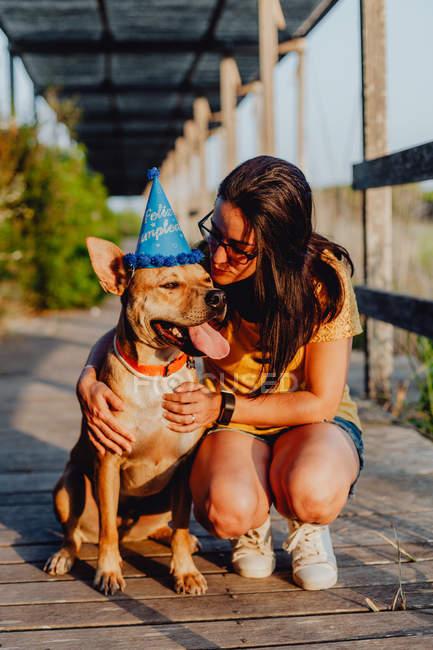 Випадкові молода жінка відпочиває поруч з коричневої собакою з партією Hat — стокове фото
