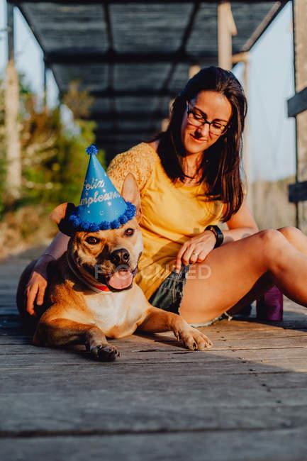 Повсякденна жінка сидить поруч з коричневим собакою в партії капелюх в сільській місцевості — стокове фото