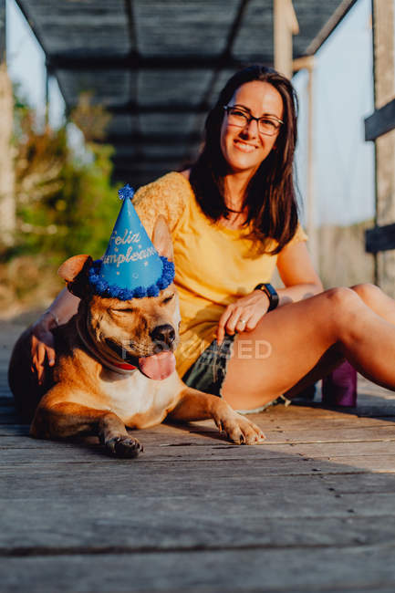 Casual woman sitting next to brown dog in party hat in countryside — Stock Photo