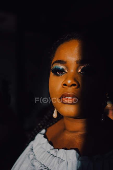 Retrato de hermosa mujer joven con curvas negras con maquillaje brillante en vestido fuera del hombro mirando a la cámara - foto de stock