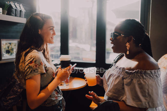 Side view of cheerful multiracial young casual women laughing and drinking coffee while sitting by window at cafe on sunset — Stock Photo
