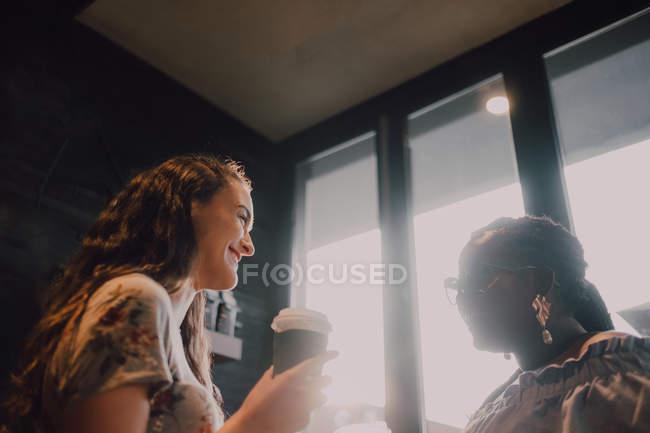 Von unten von fröhlichen, multirassischen jungen, lässigen Frauen, die lachen und Kaffee trinken, während sie am Fenster im Café bei Sonnenuntergang sitzen — Stockfoto