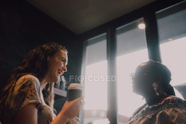 From below of cheerful multiracial young casual women laughing and drinking coffee while sitting by window at cafe on sunset — Stock Photo
