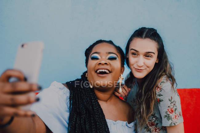 Многорасовые молодые случайные женщины смеются и делают селфи со смартфоном на светлом фоне — стоковое фото