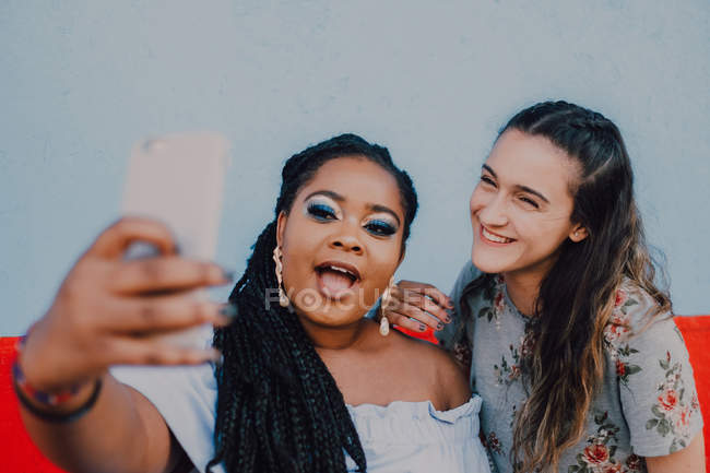 Multiracial young casual women laughing and taking selfie with smartphone on light background — Stock Photo