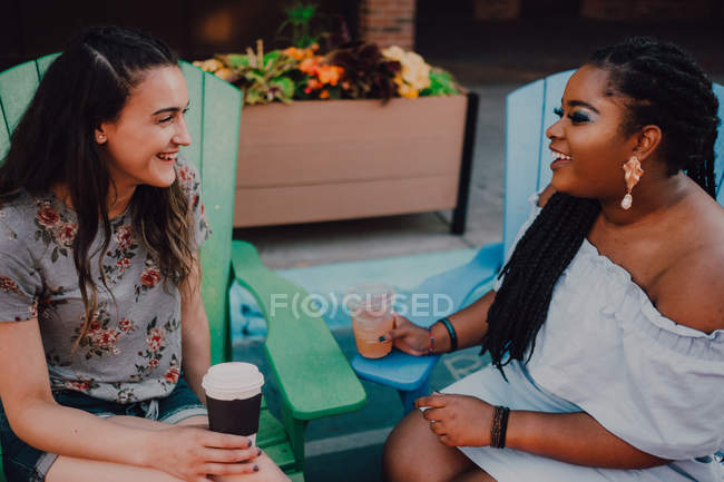Cheerful multiracial young casual women talking and drinking coffee while sitting by vibrant table at hipster cafe — Stock Photo