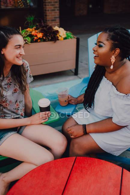 Allegro multirazziale giovani donne casual parlando e bevendo caffè mentre seduto vicino al tavolo vibrante al caffè hipster — Foto stock