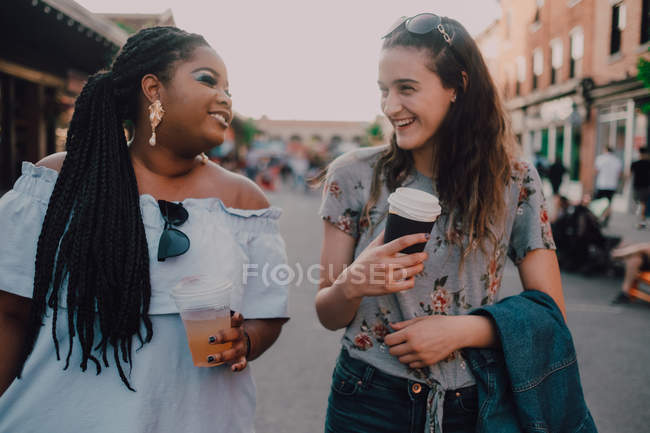 Cheerful trendy multiracial young casual women talking and drinking coffee while walking on street on sunset — Stock Photo