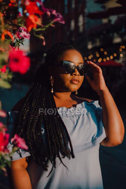 Приваблива чорна стилістична молода жінка в сукні поза плечей і сонцезахисні окуляри насолоджуються сонцем стоячи на вулиці — стокове фото