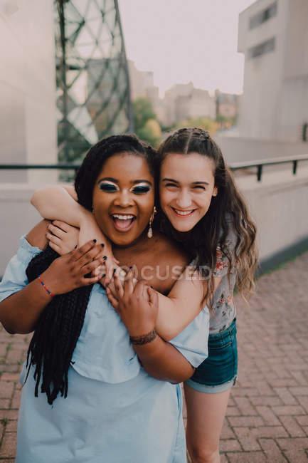 Junge Frauen lachen und umarmen sich, während sie auf der Straße stehen und in die Kamera schauen — Stockfoto