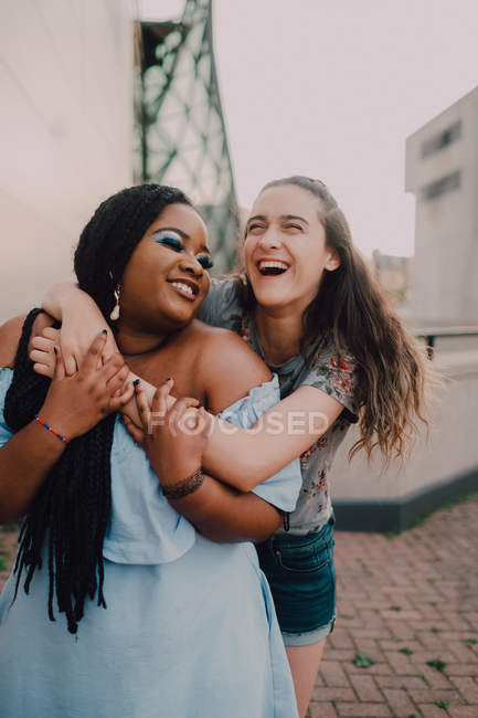 Multiracial young casual women laughing and hugging while standing on street on sunset — Stock Photo