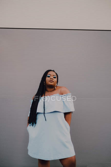 Attractive black young woman with bright makeup in off-shoulder dress standing on empty wall, looking at camera — Stock Photo