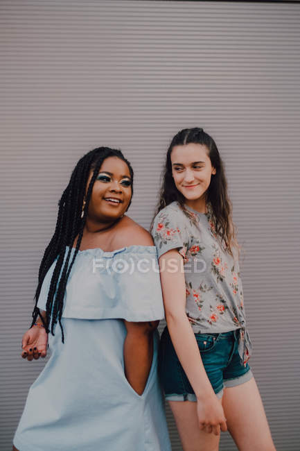 Multiracial young casual women laughing and hugging while standing on street wall — Stock Photo