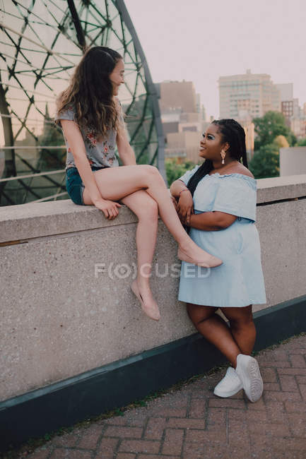 Friendly multiracial trendy young casual women having conversation while leaning on concrete parapet on sunset — Stock Photo