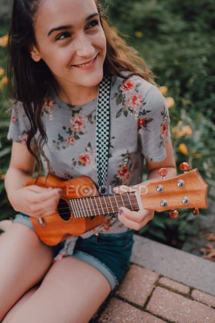 Sorrindo na moda casual jovem em t-shirt jogando ukulele enquanto sentado no pavimento ao lado de canteiro de flores — Fotografia de Stock