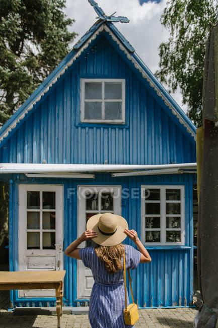 Back view of woman in straw hat and sundress standing in front of colourful blue summer house in daylight — Stock Photo