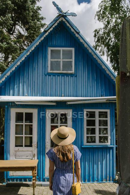Vista trasera de la mujer en sombrero de paja y vestido de sol de pie frente a la colorida casa de verano azul a la luz del día - foto de stock