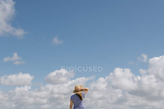 Back view of adult woman in straw hat and sundress against cloudy sky — Stock Photo