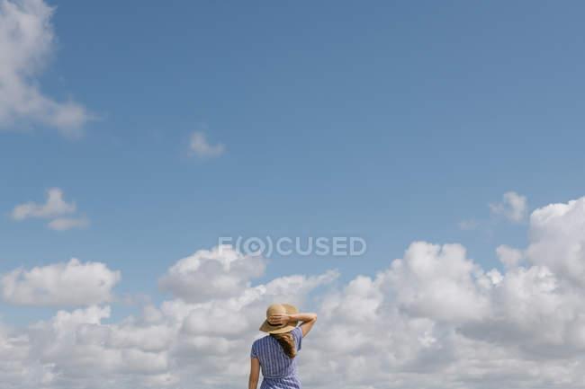 Visão traseira da mulher adulta em chapéu de palha e vestido de verão contra o céu nublado — Fotografia de Stock