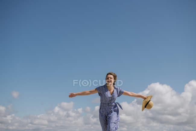 Contenuto donna adulta con capelli che soffiano e in prendisole che cammina con cappello di paglia in mano su sfondo cielo nuvoloso — Foto stock