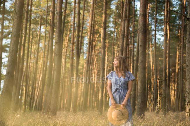 Mulher adulta feliz em chapéu de palha e sundress em pé na floresta entre árvores coníferas em raio de sol dourado — Fotografia de Stock