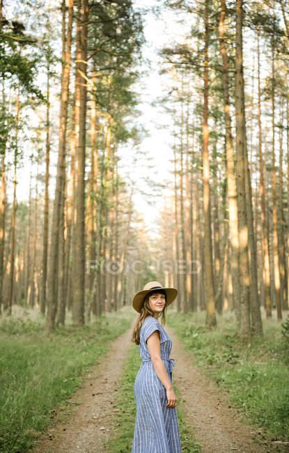 Вид на взрослую женщину в соломенной шляпе и сарафане, идущую по лесной дороге между соснами в солнечный день — стоковое фото