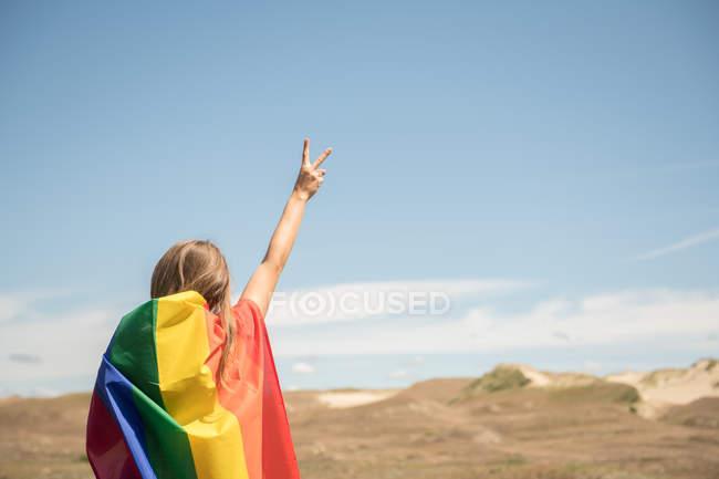 Vue arrière de la femme confiante adulte en robe décontractée portant drapeau de couleur arc-en-ciel au-dessus de la tête le jour venteux — Photo de stock