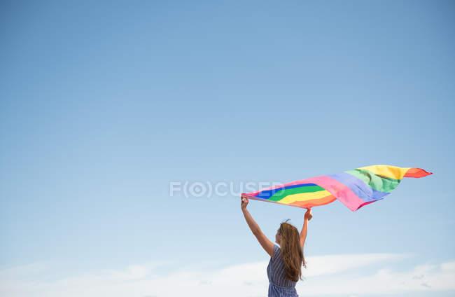 Впевненість дорослої жінки в повсякденному одязі з райдужним прапором над головою у вітряний день — стокове фото