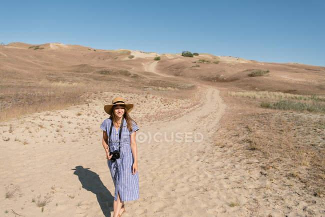 Взрослая женщина в соломенной шляпе и платье с камерой, идущей по тропинке — стоковое фото