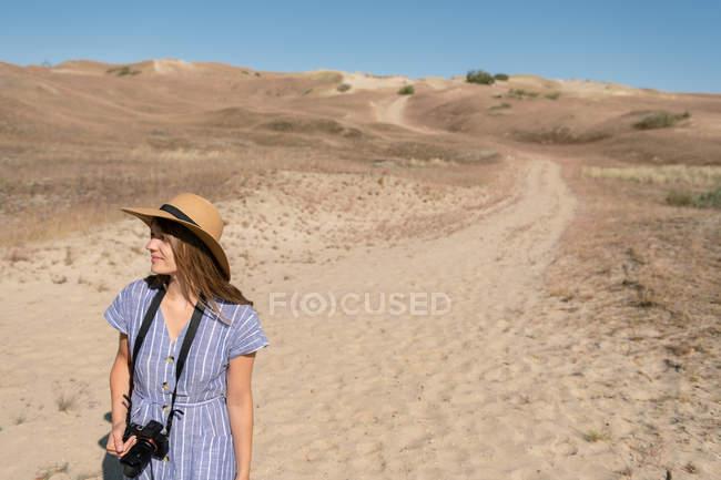 Donna adulta in cappello di paglia e vestito con macchina fotografica che cammina sul sentiero di campagna — Foto stock