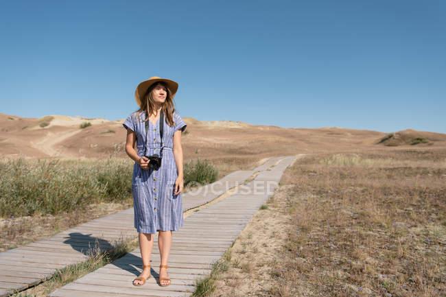 Mujer adulta en sombrero de paja y vestido con cámara de pie en el camino del país - foto de stock