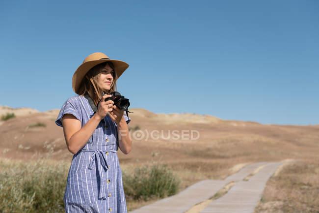 Mulher adulta em chapéu de palha e vestido com câmera em pé no caminho do país — Fotografia de Stock
