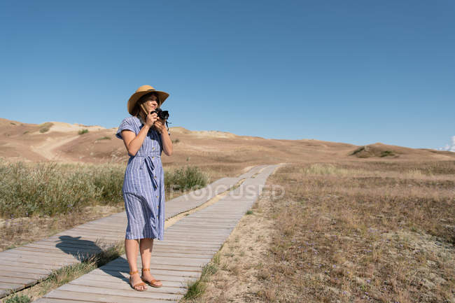 Donna adulta in cappello di paglia e vestito con macchina fotografica in piedi sul sentiero di campagna — Foto stock
