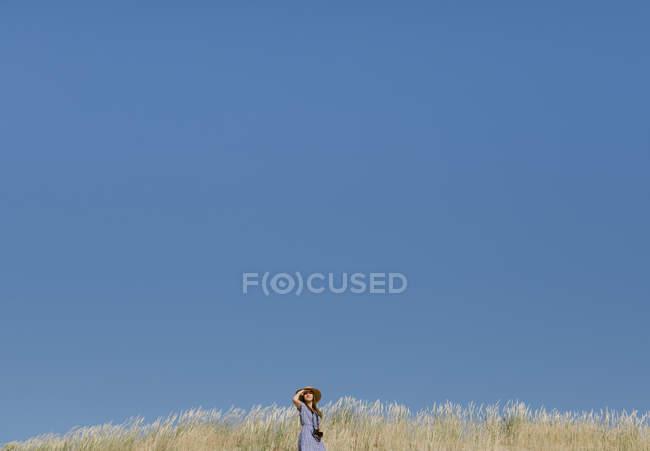 Vue arrière de la femme adulte en chapeau de paille et robe avec caméra debout sur la colline — Photo de stock
