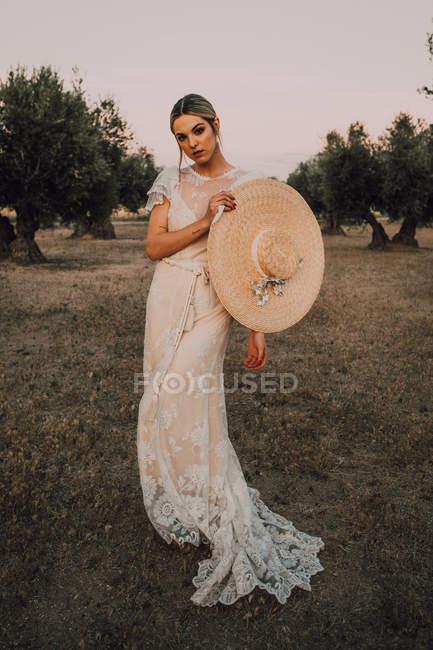 Mujer en vestido sosteniendo sombrero - foto de stock