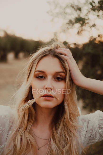 Портрет очаровательной женщины, задумчиво смотрящей в камеру с спелым ухом пшеницы во рту — стоковое фото