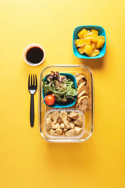Plastic containers with healthy food and black fork — Stock Photo