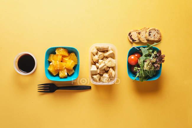 Вид сверху контейнеров с хлебом и помидорами, аругулой и кусочками апельсина, соевым соусом и куриным филе с черной пластиковой вилкой на желтом фоне — стоковое фото