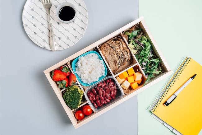 Vista superior da caixa de alimentos com morango e tomate, brócolis e feijão, arroz e trança, queijo e rúcula colocados sobre a mesa — Fotografia de Stock