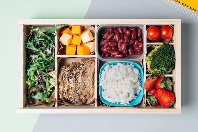 Caixa de alimentos com ingredientes dietéticos por copybook e placa — Fotografia de Stock