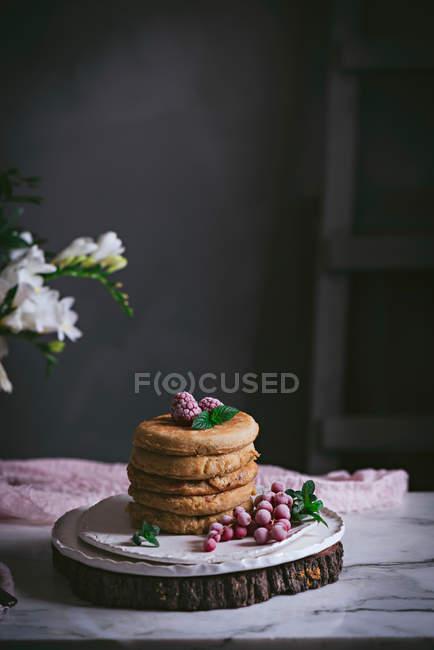 Stapel von Himbeerpfannkuchen mit frischen Beeren auf Porzellanteller über dunklem Hintergrund — Stockfoto