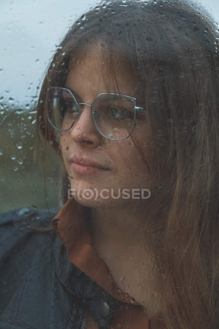 Portrait of beautiful woman with glasses looking out of wet window on rainy day looking away — Stock Photo